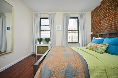 Private bedroom with queen size bed and exposed brick wall