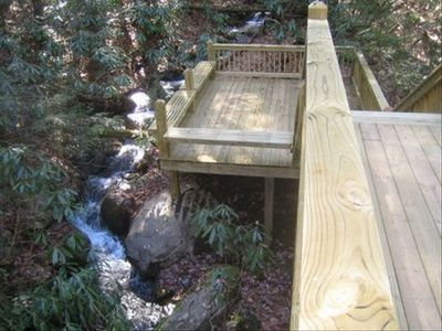 Deck with benches for relaxing creekside by several cascading small waterfalls