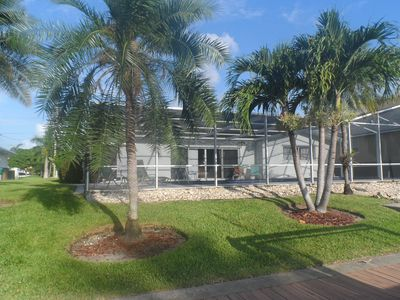 Beautifully landscaped with Palms and flora, screened Lap Pool and patio