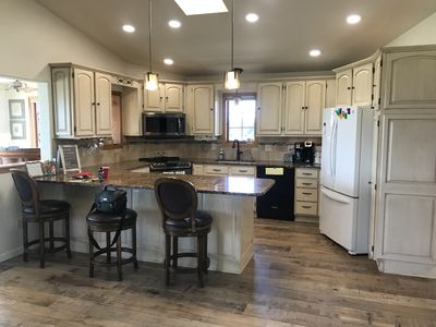 Kitchen/Gathering space opens to two sunrooms and has a eat at bar.