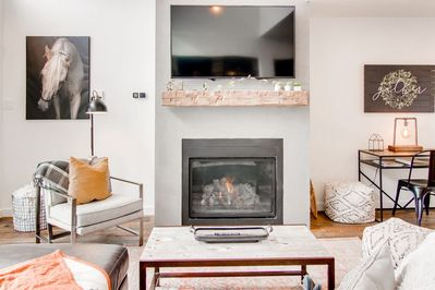 Cozy fireplace with reclaimed beam, smart tv, sectional leather couch