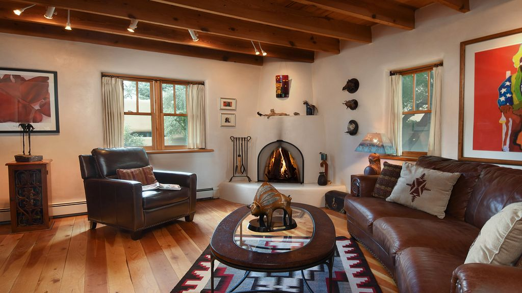 Our art-filled living room with Navajo rug, kiva fireplace and leather seating