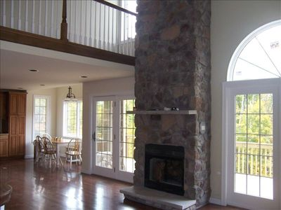 Great room with vaulted ceiling, woodburning fireplace, atrium doors to deck