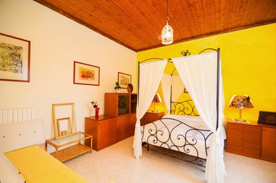 The spacious bedroom with a four-poster bed and a sofa convertible into 2 beds