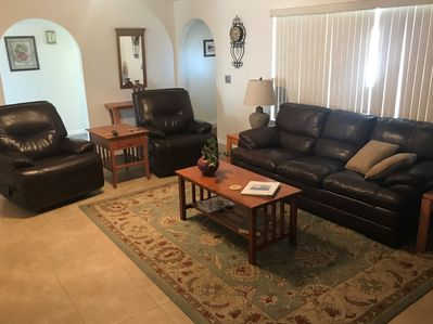Comfortably furnished living room with leather, high ceilings and lots of light