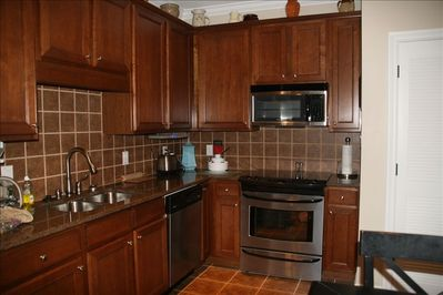 Kitchen has solid surface counters, tile floors and top of the line appliances.