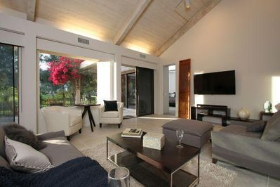 Living room facing golf course w/new 60 in. LED TV. Sliding doors lead to patio.