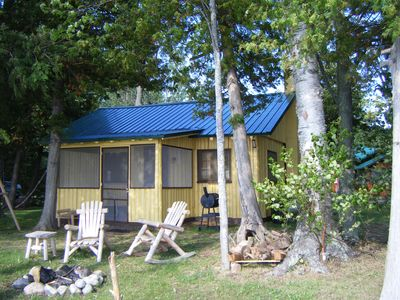Yellow cabin with screen porch and fire pit, Lodge barely visible to the right