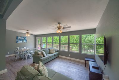 Airy living room is full of light with huge windows looking out onto the new deck and backyard