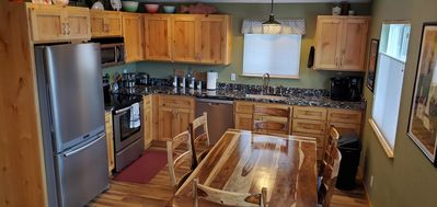 Family sized table in modern kitchen, opens into family/sitting area.