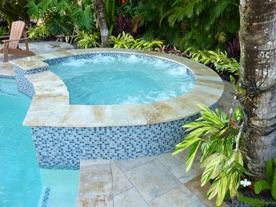 Extra large brand new 8 person spa is surrounded by hundreds of tropical plants.