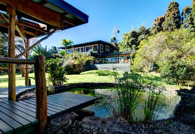 beautiful back of home with lots of decks and koi pond.