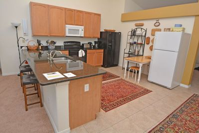 Fully equipped kitchen with small table and bar seating for 2