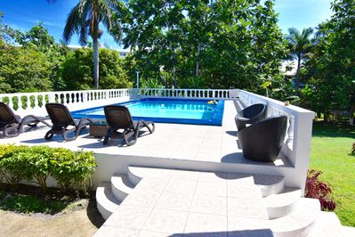 Swimming pool with four loungers also seating there is a BBQ pit on the left