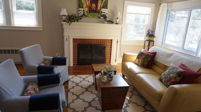 Living room with wood burning fireplace. Opposite wall is flatscreen TV.