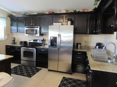 Kitchen with modern appliances and granite counter tops.  Great for family time.