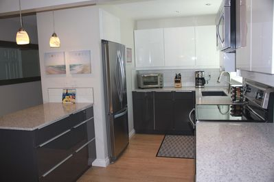 Kitchen with quartz counter tops, stainless steel appliances, ice maker.
