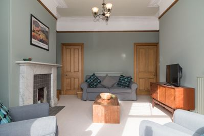 Sunny front facing lounge with beautiful woodwork and Victorian features