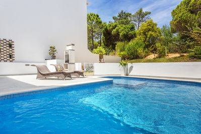Outside area featuring a heated pool with a kids section, bbq, and lounge area