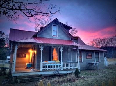 Tin Roof Cottage at dusk invites you to swing on the porch and unwind.