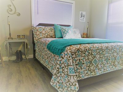 Larger of the two bedrooms with queen bed, nightstands, desk, closet