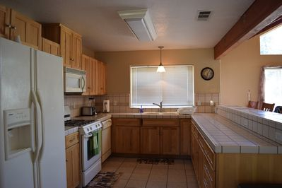 Large sunny kitchen with 4 bar stools.