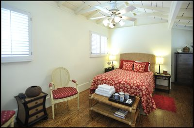 Master bedroom with open beam ceiling and fan. Small library of books in case...