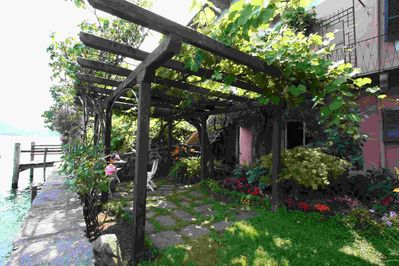 The shade of grape bower with another stone table for eating outdoors.