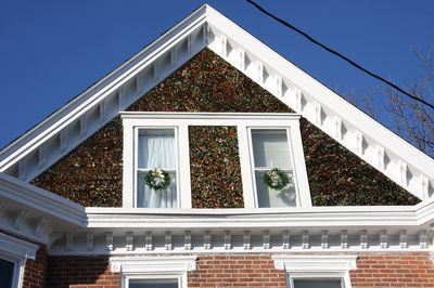 Broken glass from medicine bottles have embellished the front of the Glass Gable for more than 100 years. The glass glitters in the sunshine and has led to the name - Glass Gable.