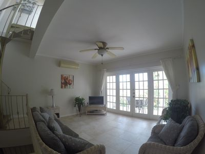 "Living room with double doors to balcony and 32"" HD Smart TV."