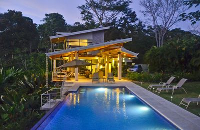 view of infinity pool with in-water bar and large covered outside living area