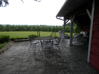 Patio with a view of the front yard, orchard and mountains in the distance