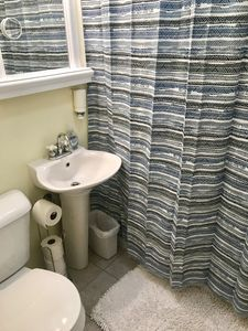 Full bathroom is adjacent to bedroom, with towels, toilet paper, soap & shampoo