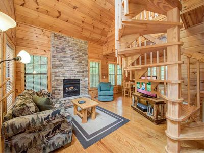 Rustic refinement - The cabin is as gorgeous inside as it is charming outside. The lustrous hardwood floors, the vaulted ceiling, the handcrafted spiral staircase, and the stone hearth add to the elegance of the open living/dining/kitchen area.