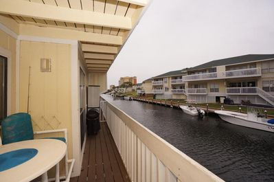 Enjoy this adorable 1-bedroom condo located directly over the canal and only steps away from the golf course, tennis courts & Louisiana Lagniappe restaurant - Comfortable high-top table and chairs on the deck - perfect for evening relaxation