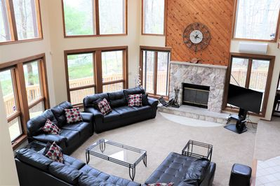 Stunning living room with walls of windows and skylights! Cable TV and fireplace