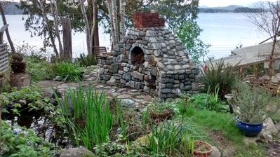 outside kitchen/fireplace and a pond