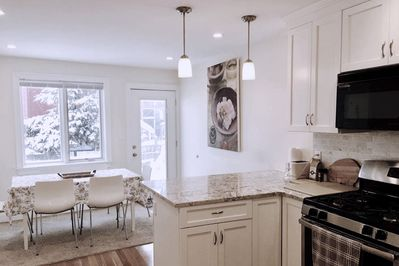 Modern granite kitchen with stainless steel appliances and open dining room