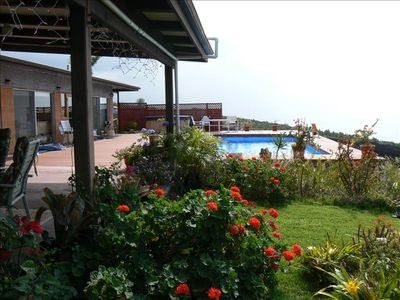 Taken from lanai showing garden pool, hot tub, and house.  Ocean in background.