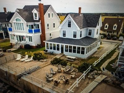 Aerial view of private oceanfront yard with firepit sitting area and furniture