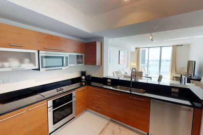 The stunning kitchen features granite counters, European style cabinetry, and upgraded stainless steel appliances.