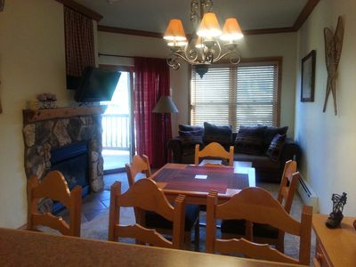 From the kitchen, view of dining table, fireplace, television and sofa.