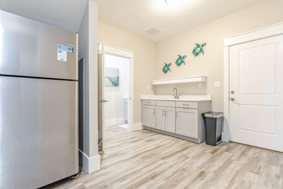 Down the hall on the first floor is a second refrigerator and half bath.