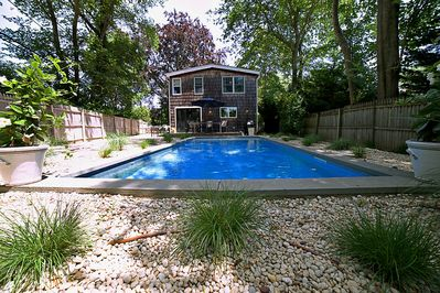 large in ground pool with seating for 4 and back porch with table seats 6 to 8