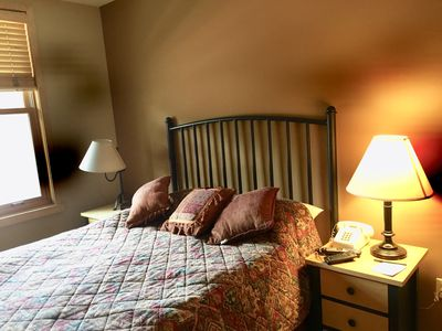 Private bedroom with queen bed and television.