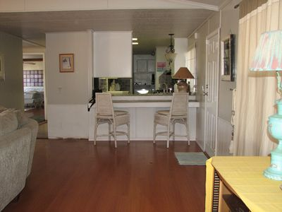 Breakfast nook off living room with pass-thru to kitchen and washer/dryer beyond
