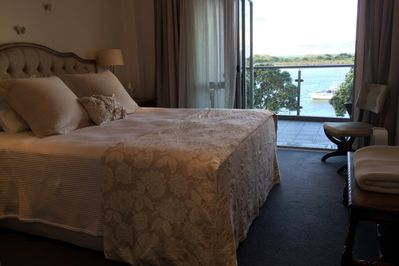 Main bedroom showing balcony access and water view