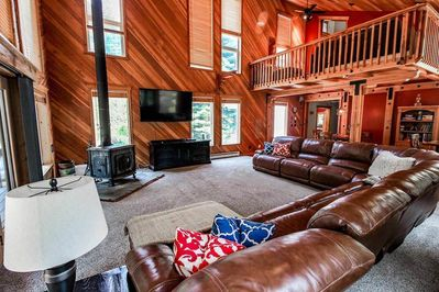 Large brown leather sectional couch next to a wood stove and mounted TV