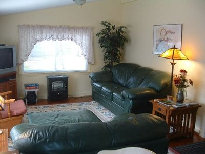 Living room with leather furn.,electric fireplace, t.v., etc.