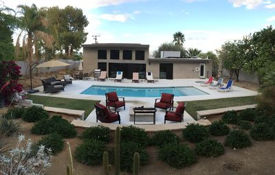 Day time view of backyard pool area.  7 Chaise lounges, 2 tables, 2 seating area